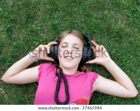 Girl lying on the grass and listening to music - stock photo