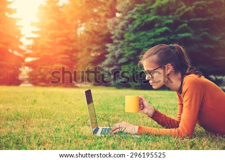 girl lying on the grass and using laptop and typing with coffee or tea mug. copy space - stock photo