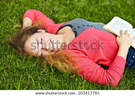 girl lying on the grass in the park and reading a book.  youth lifestyle