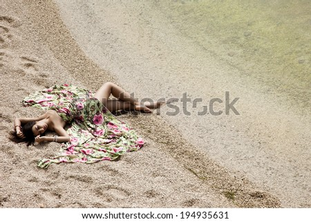 girl lying on the sand by the sea - stock photo