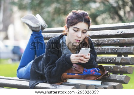 Girl lying on wood bench and reading message on phone, adolescence lifestyle concept, outdoor. - stock photo