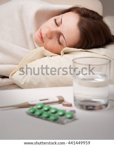 girl lying sleep in bed near  sick medicines on table in room
