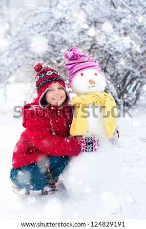 Girl makes a snowman outside in winter time - stock photo