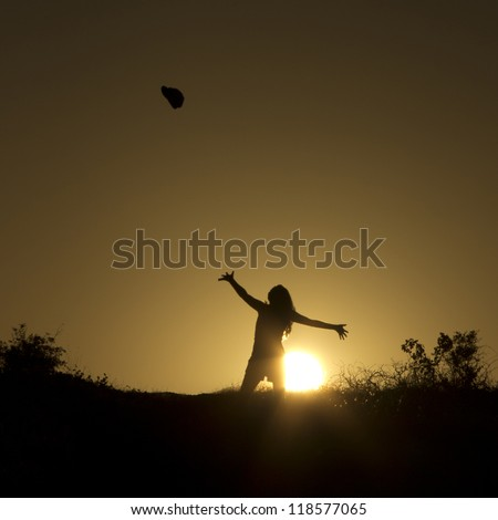 Girl makes the graceful throw at sunset - stock photo