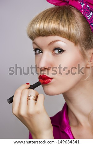 girl makes up lips with red lipstick on a gray background - stock photo