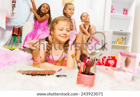 Girl makeup with brush and her friends behind - stock photo