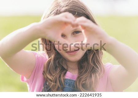 girl making a love heart sign - stock photo