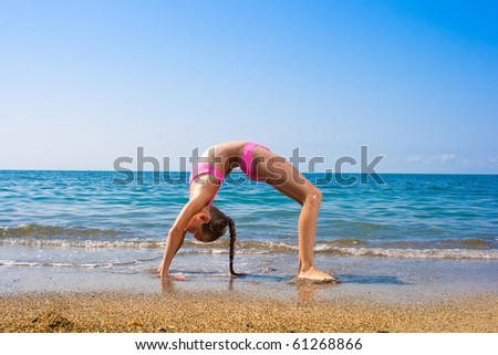 girl making exercise or gymnastics on seashore