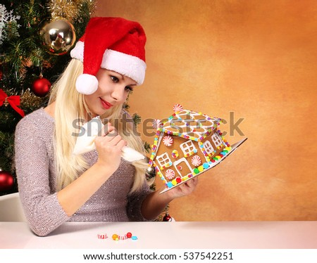 Girl making gingerbread house. Young woman with Santa Hat. Christmas Preparations