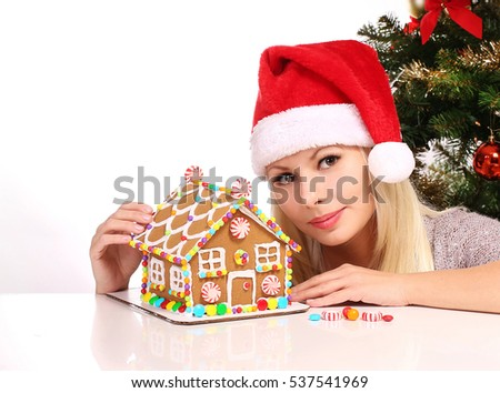 Girl making gingerbread house. Young woman with Santa Hat isolated on white. Christmas Preparations