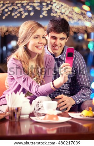 Girl making photo with her boyfriend in cafe