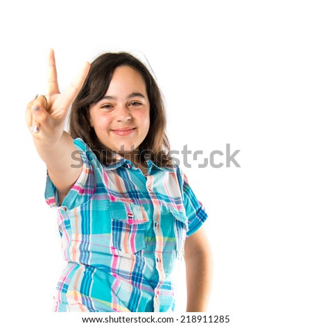 Girl making victory sign over white background  - stock photo