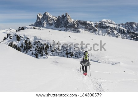 Girl marching along mountain ridge in the Dolomites during Winter - stock photo