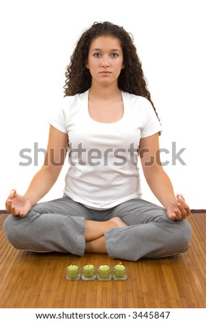 Girl meditating, fragrant candles helping her to relax - stock photo