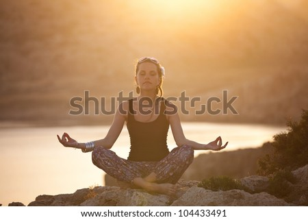 girl meditating in sunset. girl sitting on a rock in the lotus pose - stock photo