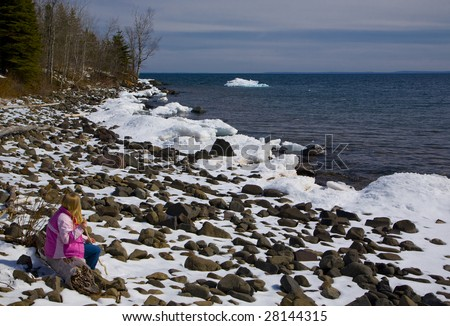 Girl meditating on a snow beach on Stony Point along the North Shore of Lake Superior in Minnesota. - stock photo