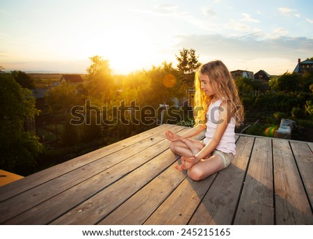 Girl meditating outdoors. Child practicing yoga - stock photo