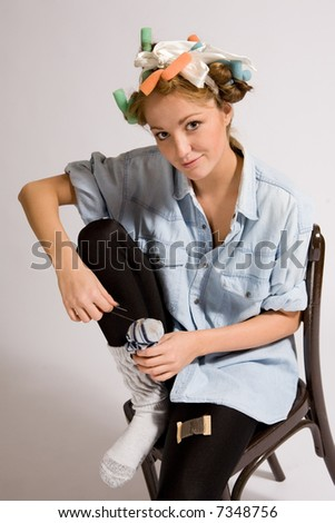 Girl mending socks with hair curlers. - stock photo