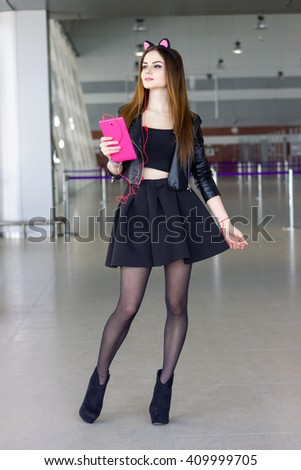 Girl model wearing cat ears holding pink tablet and listen music. Indoor young female portrait wearing leather jacket and black skirt. Fashion lady with long brown hair wear cool outfit and high heels - stock photo
