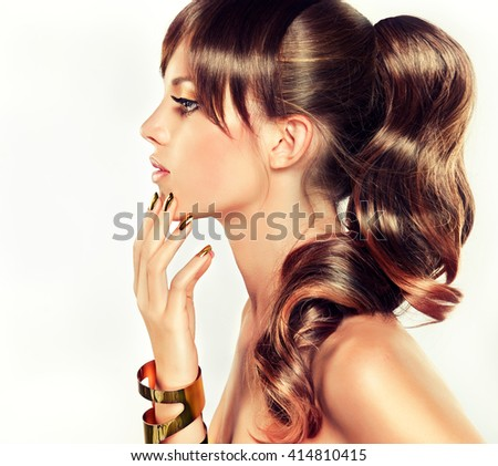 Girl model with  Golden makeup and gold  metal manicure  nails. Cosmetics,makeup and beauty . Long curly hair ,hairstyle  tail  with bangs  .
