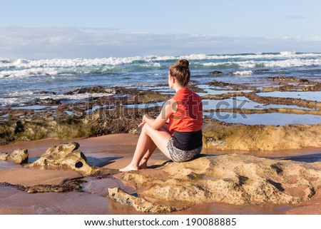 Girl Morning Beach Ocean Young teen girl on beach coastline rocks sits watching morning ocean waves with playtime fun to relax. - stock photo