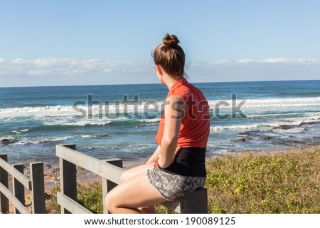 Girl Morning Beach Ocean Young teen girl on beach coastline walkway steps sits watching morning ocean waves with playtime fun to relax. - stock photo