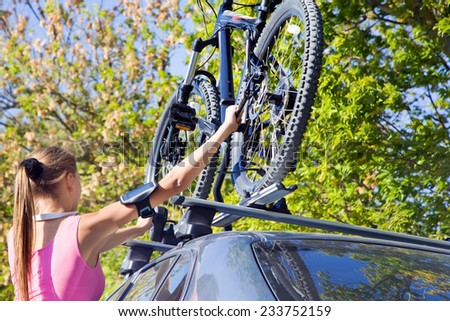 Girl mounted  transportation bikes on the roof of a car on a sunny day - stock photo