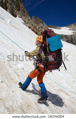 Girl moving down on snow with rope belay - stock photo