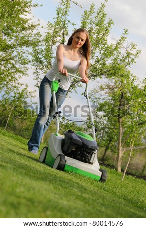 Girl mows the lawn - stock photo