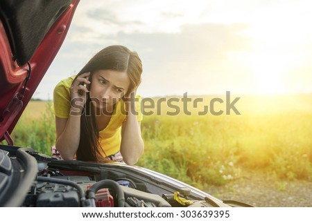 Girl near a broken car on the country road is calling on mobile phone. - stock photo