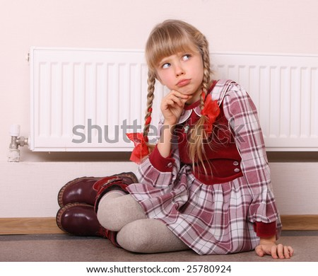 Girl near radiator. Energy crisis. - stock photo