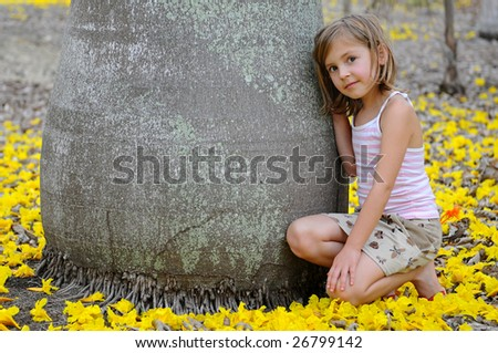 Girl near the big tree surrounded by yellow flowers - stock photo