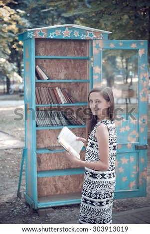 girl near the bookcase in the park - stock photo