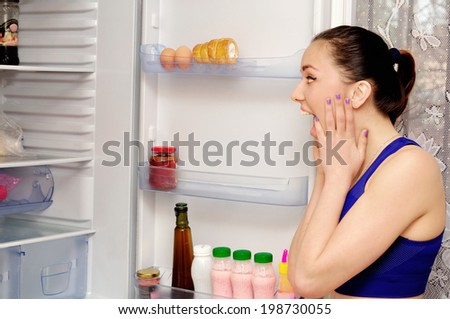Girl near the open refrigerator shouts - stock photo