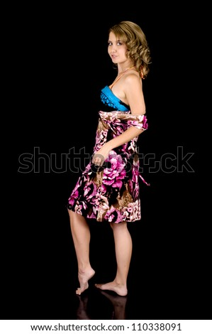 Girl-next-door beauty removing her dress to reveal a sarong. - stock photo