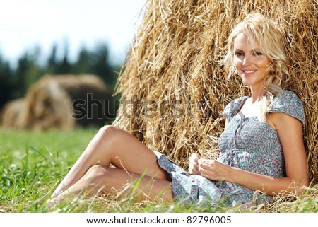 girl next to a stack of hay - stock photo