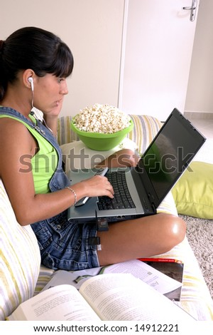 Girl of generation Y doing many things at the same time (calling,  watching tv, Surfing the web and eating popcorn) - stock photo