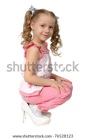 girl of 5-6 years dressed in the big mum's shoes, on a white background. - stock photo
