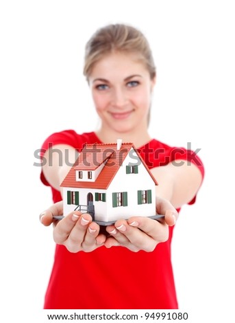 Girl offering a miniature house for us, concept - stock photo
