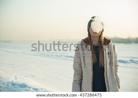 girl on a background of snow smokes an electronic cigarette