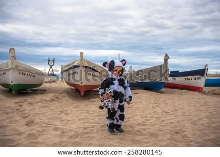 girl on a beach dress up as a cow - stock photo