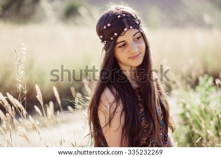 Girl on a beautiful field with a flower garland on a summer day - stock photo
