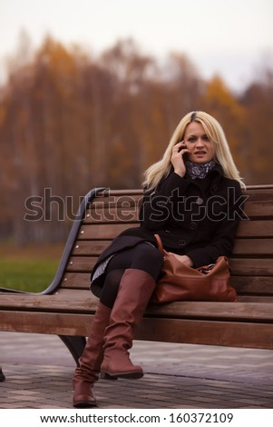 girl on a bench talking on the phone