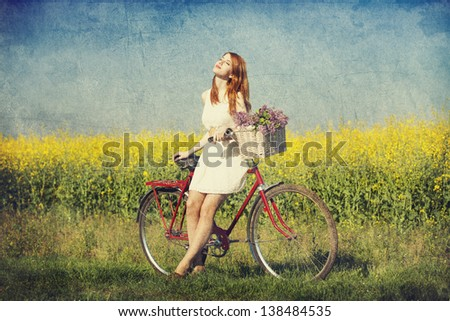 Girl on a bike in the countryside. - stock photo