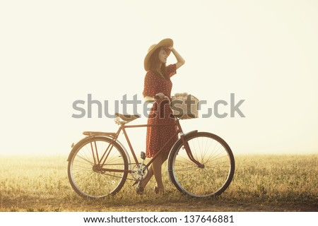 Girl on a bike in the countryside in sunrise time. - stock photo
