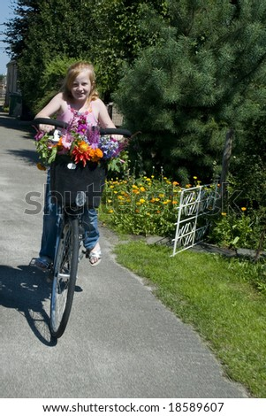 Girl on a bike with flowers in the summer - stock photo