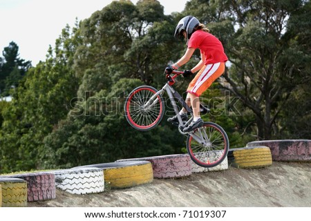 Girl on a bmx bike doing a jump over the tires on the track - stock photo