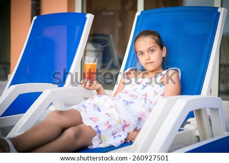 girl on a deckchair drinking juice. Girl and orange juice, summer vitamin drink - stock photo