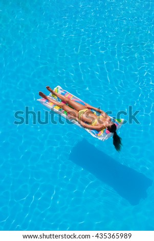 Girl on a lilo in resort swimming pool