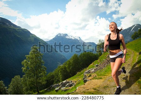 girl on a morning jog in the summer outdoors. Geiranger autumn. scenic landscapes of the northern Norwegian fjords. - stock photo